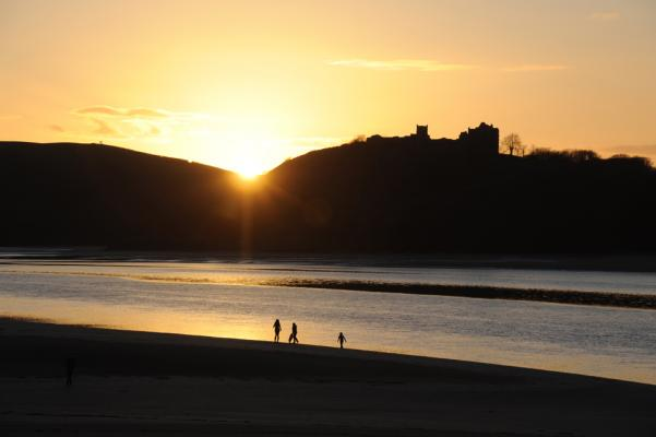 A family plays on the beach at low tide as the sun falls behind Llansteffan Castle March 2011